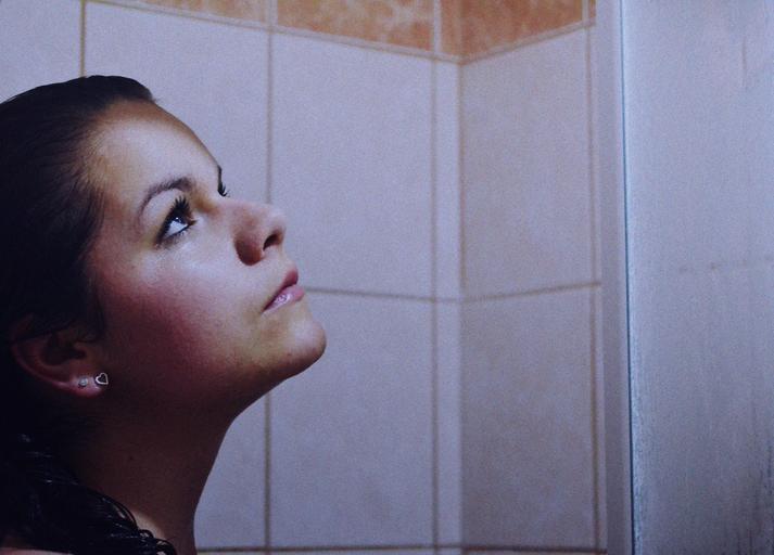 Žena  s čiernymi vlasmi stojí v sprchovom kúte